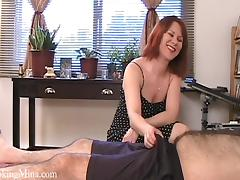 Horny redhead jerks a guy off while showing her tits