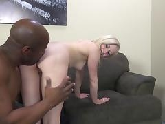 Blonde with a shaved pussy enjoying a mind-blowing interracial fuck on her sofa