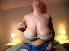 Blonde slut playing her big boobs on the bed